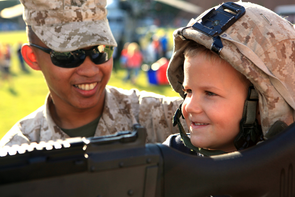 Lance Cpl. JuanCarlos Aglugub, a Light Armored Vehicle crewman at 4th Light Armored Reconnaissance Battalion in Marine Corps Base Camp Pendleton, Calif., Special Purpose Marine Air Ground Task Force Marine Week shows a young Cardinal fan what it's like to be hold a machine gun outside Busch Stadium in St. Louis June 21, 2011. Marines from all across the Corps came to St. Louis for Marine Week to show the city who they are and what they do. Photo by Lance Cpl. Chelsea Flowers