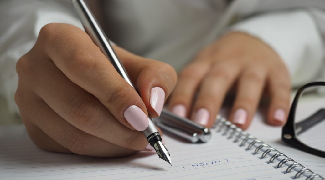 Photo of woman with a pen and paper notebook